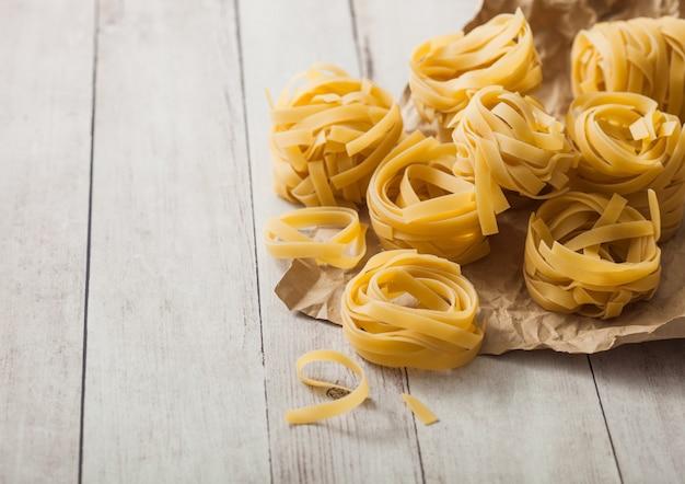 Zelfgemaakte tagliatelle pasta in bruin papier op witte houten achtergrond.