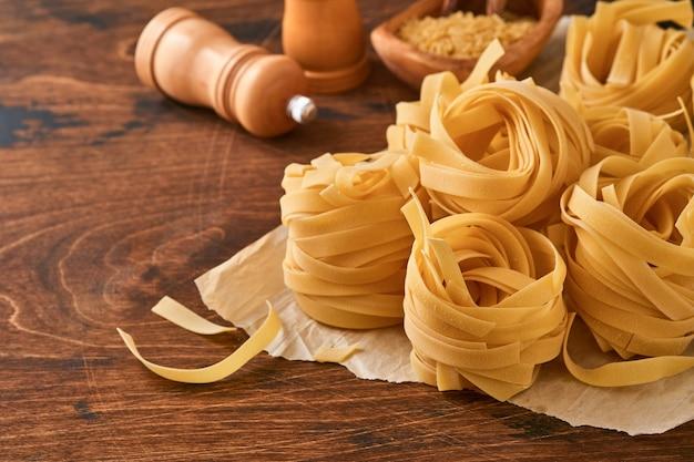 Zelfgemaakte tagliatelle pasta in pakpapier op een oude houten achtergrond.