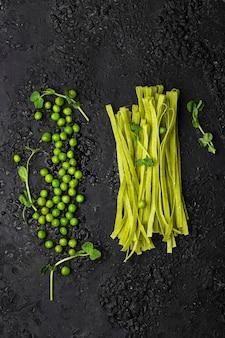 Zelfgemaakte tagliatelle-pasta met fijngestampte jonge groene erwten op zwart
