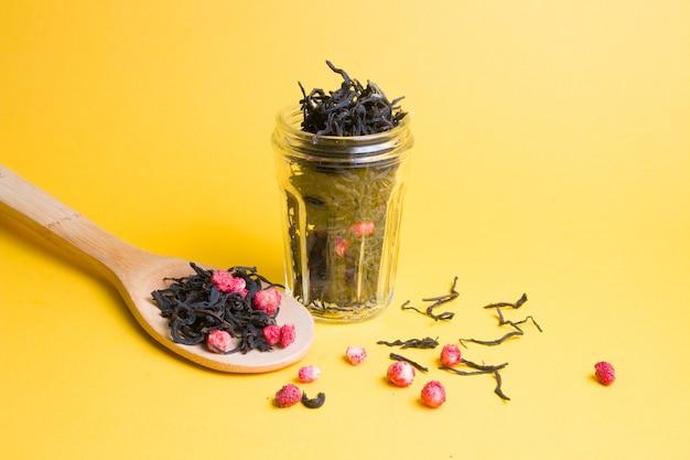 Zelfgemaakte thee met gedroogde aardbeien in een glazen pot op een gele achtergrond, een grote houten lepel met aardbeienthee, besprenkelde thee en gedroogde aardbeien, kopieer ruimte