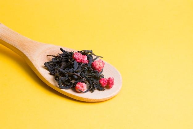 Zelfgemaakte thee met gedroogde aardbeien in een grote houten lepel op een gele ondergrond