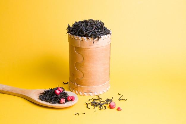 Zelfgemaakte thee met gedroogde aardbeien in een pot berkenschors op een gele achtergrond