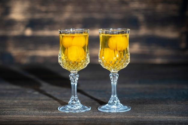 Zelfgemaakte tinctuur van gele kersenpruim in een twee wijnkristallen glas op houten tafel, oekraïne, close-up. berry alcoholische dranken concept