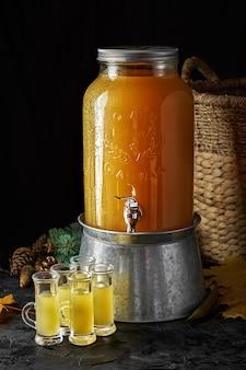 Zelfgemaakte tinctuur van gember of bier op een donkere achtergrond. landelijke stijl. pittige gele likeur in shots.