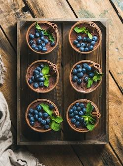 Zelfgemaakte tiramisu dessert met kaneel en bessen in houten lade