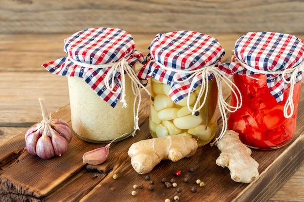 Zelfgemaakte tomatenconserven in glazen potten in witte rieten mand op houten ondergrond.