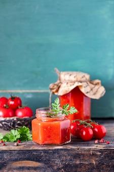 Zelfgemaakte tomatenketchup gemaakt van rijpe rode tomaten in glazen potten met ingrediënten op een oude houten tafel. kopieer ruimte