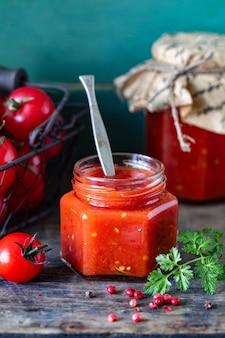 Zelfgemaakte tomatenketchup gemaakt van rijpe rode tomaten in glazen potten met ingrediënten op een oude houten tafel.