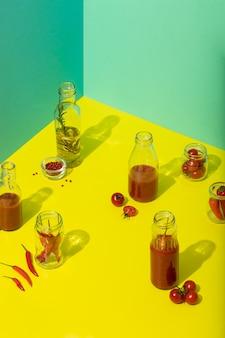 Zelfgemaakte tomatensaus en olijfolie in glazen flessen op trendy gele verse tomaten en peper van hoge kwaliteit foto