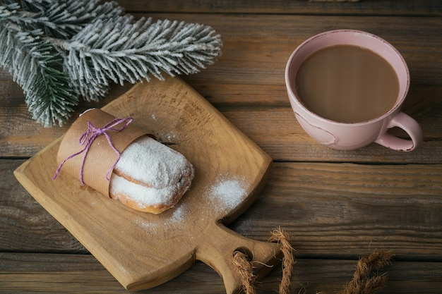 Zelfgemaakte traditionele kerstdessert stol met gedroogde bessen, noten en poedersuiker bovenop staat op rustieke houten tafel