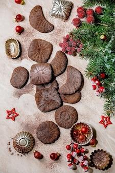 Zelfgemaakte traditionele kerstkoekjes met zanddeeg chocolade crescents met cacaoglazuursuiker met koekjesvormen, dennenboom, rode kerststerren decoraties. roze marmeren oppervlak. plat leggen