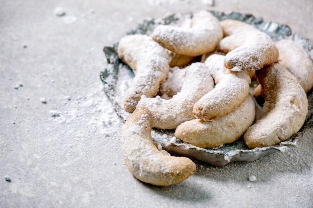 Zelfgemaakte traditionele kerstkoekjes vanille-crescents met poedersuiker. op keramische plaat over lichtgrijs oppervlak. detailopname