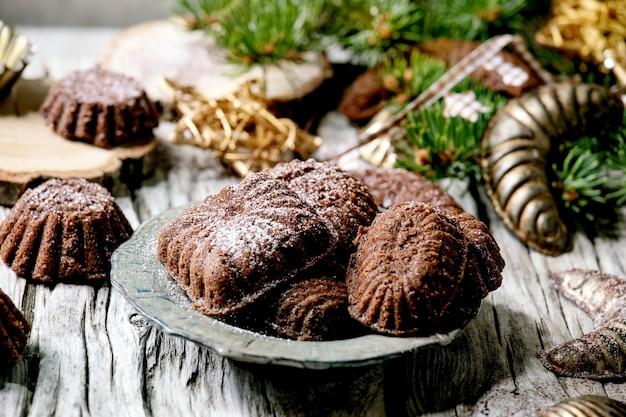 Zelfgemaakte traditionele kerstkruiddeegkoekjes chocolade halve manen met cacaosuikerglazuursuiker in keramische plaat met koekjesvormen, fir tree, xmas sterren decoraties over houten oppervlak. detailopname