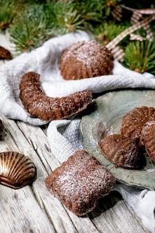 Zelfgemaakte traditionele kruimeldeeg kerstkoekjes chocolade halve manen met cacao poedersuiker in keramische plaat met cookie mallen, fir tree, xmas sterren decoraties op houten achtergrond