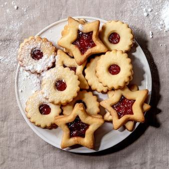 Zelfgemaakte traditionele linz zandkoek koekjes koekjes met rode jam en poedersuiker op keramische plaat over linnen tafelkleed. platliggend, ruimte, vierkant beeld
