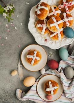 Zelfgemaakte traditionele warme kruisbroodjes van pasen en beschilderde eieren op een grijze ondergrond