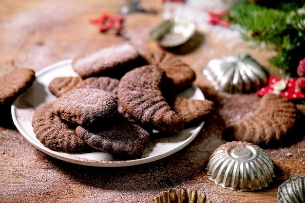 Zelfgemaakte traditionele zandkorst koekjes chocolade halve manen met cacaosuikerglazuur suiker in keramische plaat met koekjesvormen, spar, rode kerststerren decoraties over houten oppervlak. detailopname