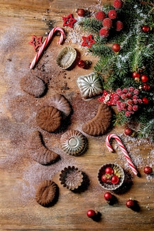 Zelfgemaakte traditionele zandkorst koekjes chocolade halve manen met cacaosuikerglazuur suiker in keramische plaat met koekjesvormen, spar, rode kerststerren decoraties over houten oppervlak. plat leggen