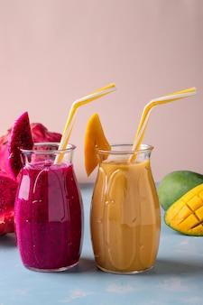 Zelfgemaakte tropische fruitsmoothies gemaakt van dragon en mango op een roze achtergrond, verticale oriëntatie