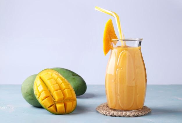 Zelfgemaakte tropische smoothie van mango op een lichtblauwe achtergrond, horizontale oriëntatie, close-up