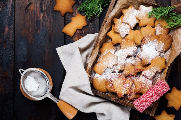 Zelfgemaakte van de de stervorm van het kerstmisnieuwjaar peperkoekkoekjes in houten doos op oude houten uitstekende oppervlakte Premium Foto