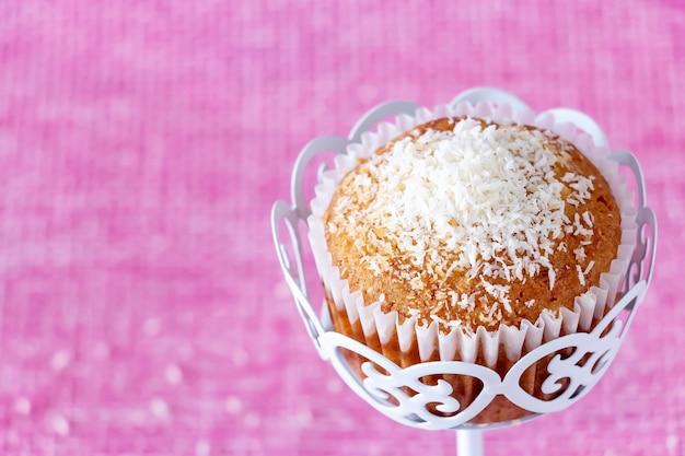 Zelfgemaakte vanille muffin met kokos poeder roze achtergrond kopieer ruimte selectieve focus