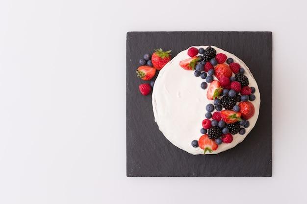 Zelfgemaakte vanille verjaardagstaart versierd met bessen aardbeien bosbessen frambozen aan boord