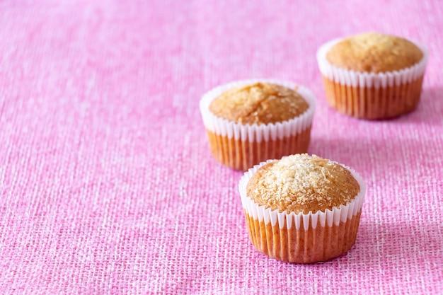 Zelfgemaakte vanillemuffins met kokospoeder roze achtergrond kopieerruimte selectieve fcus