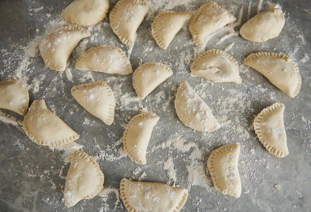 Zelfgemaakte varenyky-knoedel, traditionele oost-europese gerechten voor het koken.