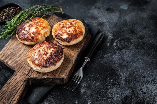 Zelfgemaakte varkens- en rundvleeskoteletten of gehaktballen op een houten bord. zwarte achtergrond. bovenaanzicht. ruimte kopiëren.