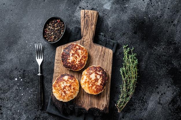 Zelfgemaakte varkens- en rundvleeskoteletten of gehaktballen op een houten bord. zwarte achtergrond. bovenaanzicht.
