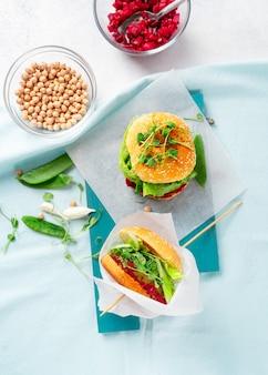 Zelfgemaakte vegan hamburgers met kikkererwten pattie, doperwtjes en rode bietensalsa