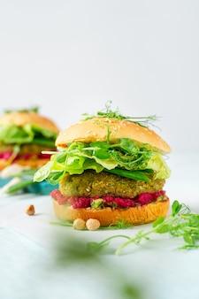 Zelfgemaakte vegan hamburgers met kikkererwten pattie, groene erwten en bieten hummus met kopie ruimte