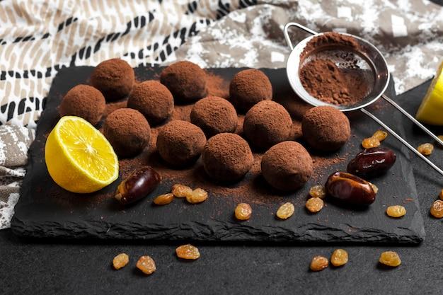 Zelfgemaakte vegan truffels met gedroogd fruit, walnoten en rauwe cacaopoeder geserveerd op zwarte leisteen plaat