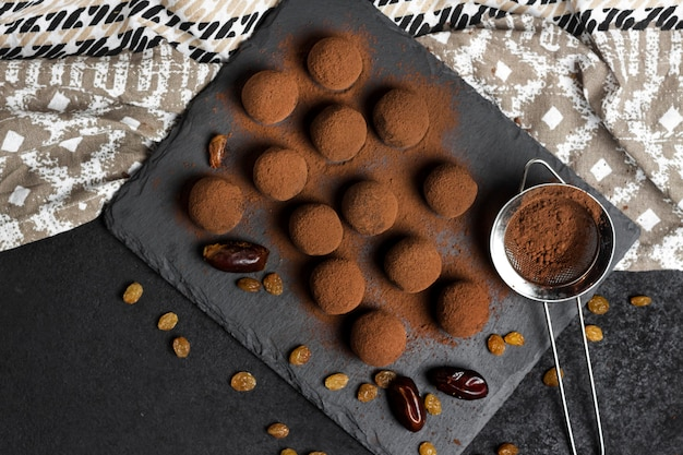 Zelfgemaakte vegan truffels met gedroogd fruit, walnoten en rauwe cacaopoeder geserveerd op zwarte leisteen plaat.