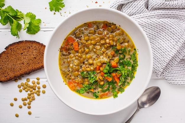 Zelfgemaakte veganist linzensoep met groenten, brood en koriander, witte houten achtergrond.