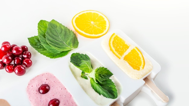 Zelfgemaakte veganistische diversiteit aan ijslolly's van kers, munt, sinaasappel, koffie en kokosmelk. natuurlijk fruit en bessenroze roomijs zonder suiker.