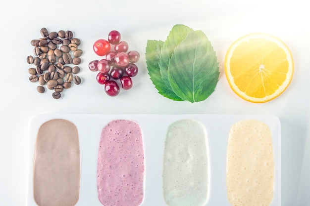 Zelfgemaakte veganistische diversiteitsijsjes van kersen, munt, sinaasappel, koffie en kokosmelk. natuurlijk fruit en bessenroze roomijs zonder suiker. achtergrondverlichting