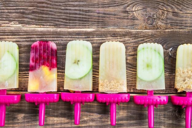 Zelfgemaakte veganistische ijslolly van frozen apple juice and berries