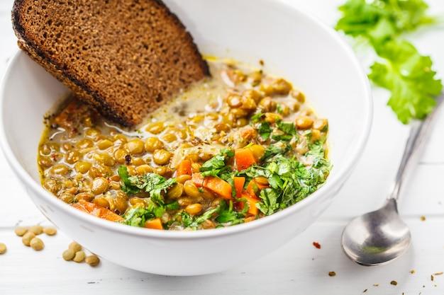 Zelfgemaakte veganistische linzensoep met groenten, brood en koriander