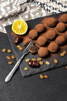 Zelfgemaakte veganistische truffels met gedroogd fruit, walnoten en rauw cacaopoeder geserveerd op zwarte leisteenplaat. kopieer ruimte