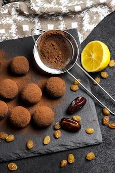 Zelfgemaakte veganistische truffels met gedroogd fruit, walnoten en rauw cacaopoeder geserveerd op zwarte leisteenplaat. plat lag, bovenaanzicht.