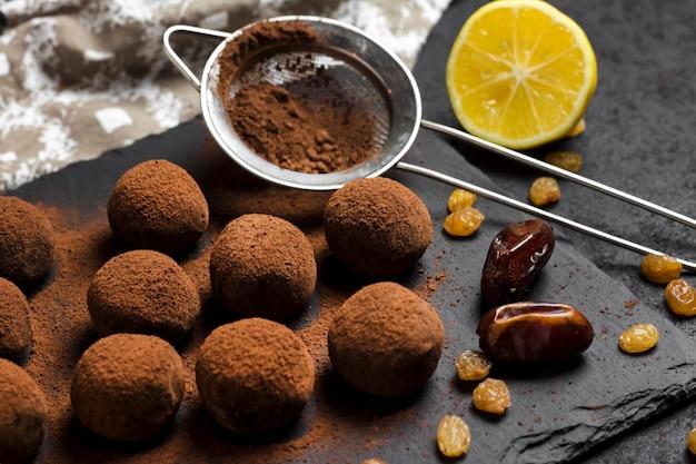 Zelfgemaakte veganistische truffels met gedroogd fruit, walnoten en rauw cacaopoeder geserveerd op zwarte leisteenplaat.