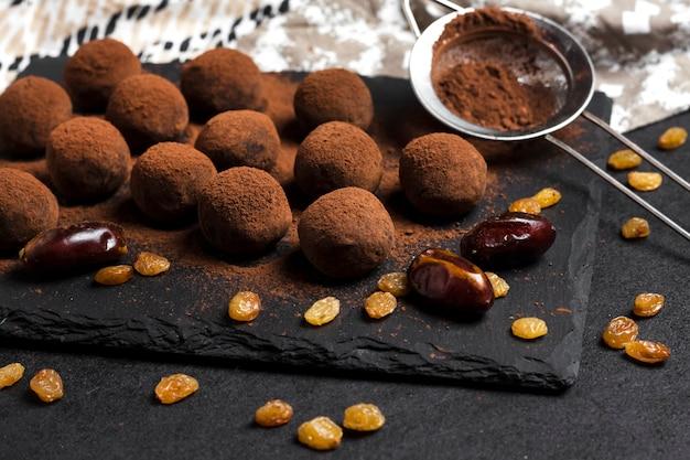 Zelfgemaakte veganistische truffels met gedroogd fruit, walnoten en rauw cacaopoeder geserveerd op zwarte leisteenplaat