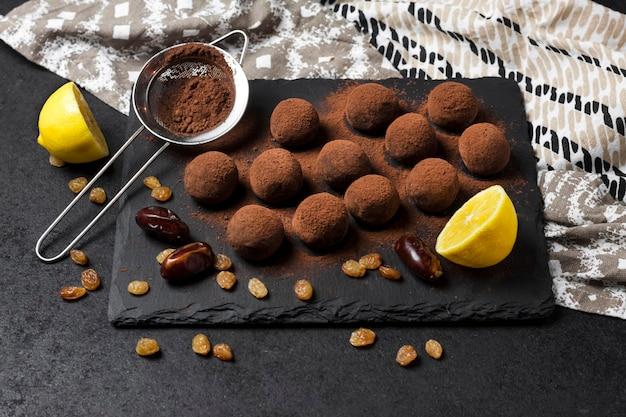 Zelfgemaakte veganistische truffels met gedroogde vruchten, walnoten en rauw cacaopoeder geserveerd op zwarte leisteen plaat.