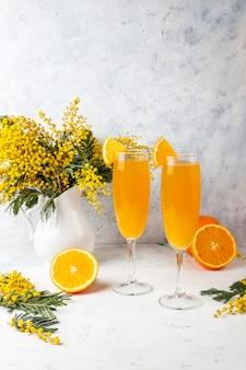 Zelfgemaakte verfrissende oranje mimosa-cocktails met champaigne