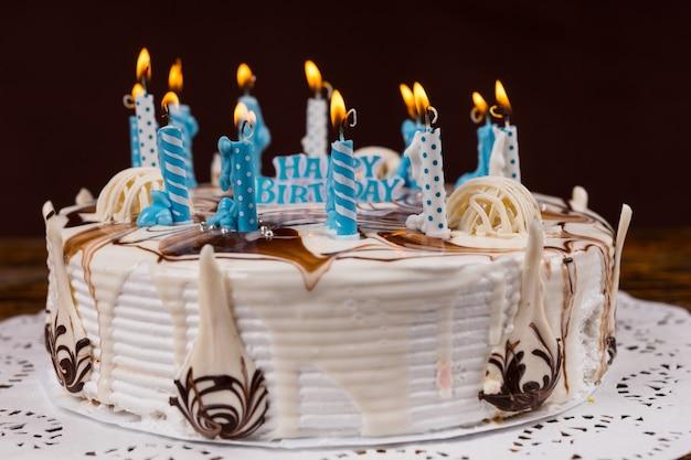 Zelfgemaakte verjaardagstaart met veel blauwe brandende kaarsen in de buurt van verschillende gekleurde macarons op wit servet