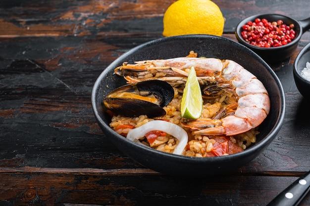 Zelfgemaakte vers bereide paella met gamba's, mosselen en inktvis in zwarte kom op oude donkere houten achtergrond