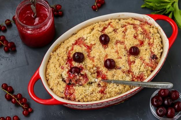 Zelfgemaakte verse cherry crumble taart met volkoren meel in keramische vorm op een donkere achtergrond
