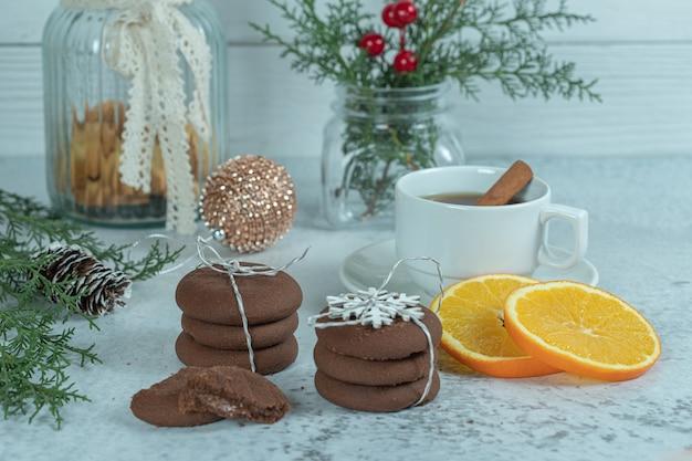 Zelfgemaakte verse chocolade koekjes en stukjes sinaasappel met kerstversiering.
